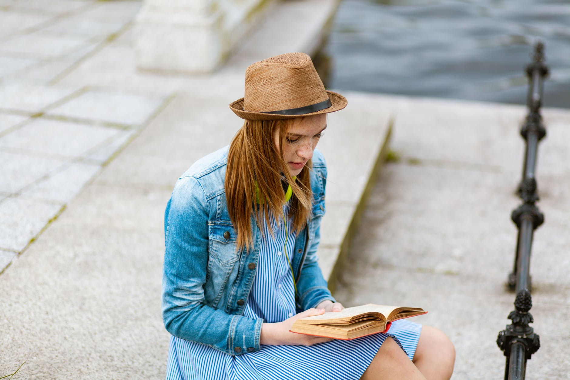 woman sitting on grey concrete pavement reading book